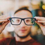 man tar av glasögon